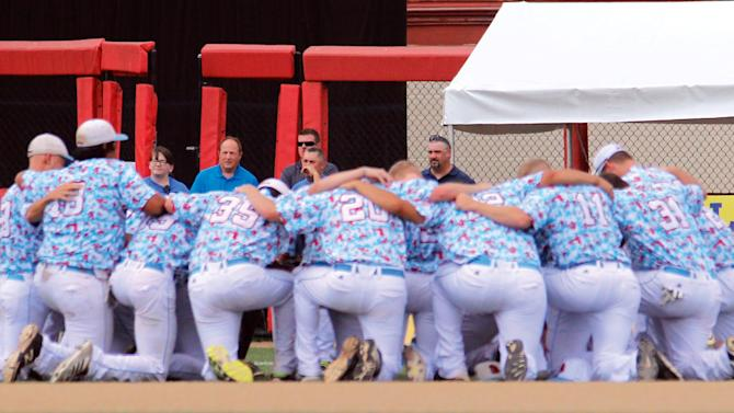 In this Aug. 1, 2015, photo, the Liberal Bee Jays team kneels in prayer near the outfield gate opened for an ambulance to transport Kaiser Carlile to a hospital at a National Baseball Congress World Series game in Wichita, Kan. Bee Jays' 9-year-old batboy Kaiser Carlile, who was wearing a helmet, was accidentally hit in the head during the game by a follow-through swing near the on-deck circle. He died on Sunday. (Earl Watt/Leader & Times via AP) MANDATORY CREDIT