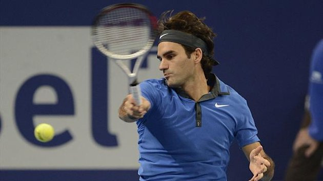 Switzerland&#39;s Roger Federer returns a ball to France&#39;s Paul-Henri Mathieu during their semifinal match at the Swiss Indoors tennis tournament at the St. Jakobshalle in Basel