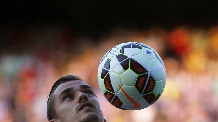 Atletico Madrid's newly signed French soccer player Antoine Griezmann controls a ball during a media presentation at the Vicente Calderon stadium in Madrid