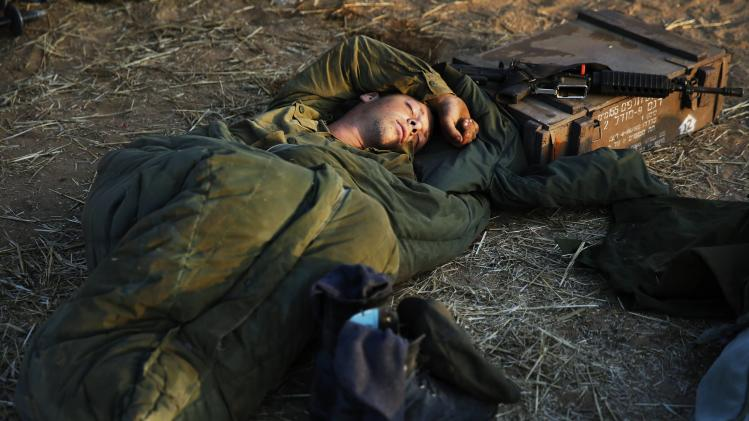 An Israeli soldier sleeps in a field near the central Gaza Strip