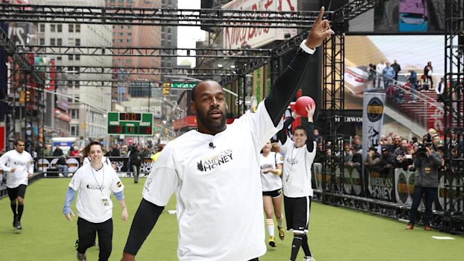 IMAGE DISTRIBUTED FOR AMERICAN HONEY - Pro football legend Donovan McNabb scores the winning point at the American Honey Bar-sity Athletics kickball game in Times Square, on Tuesday, April, 23, 2013 in New York City, New York. (Photo by Mark Von Holden/Invision for American Honey/AP Images)