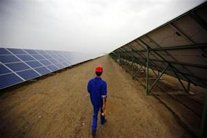A worker inspects solar panels at a solar farm in Dunhuang