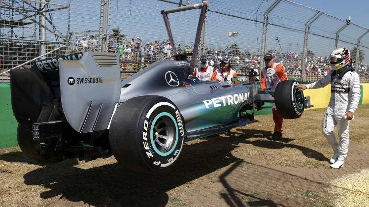 Mercedes Formula One driver Hamilton of Britain touches the wheel of his car after it broke down during the first practice session of the Australian F1 Grand Prix in Melbourne