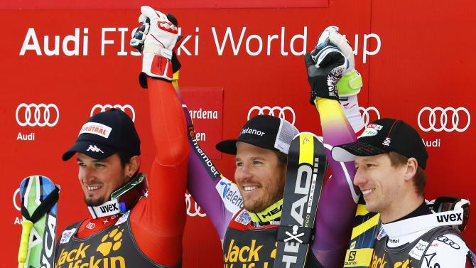 First placed Jansrud of Norway celebrates on the podium with second placed Paris of Italy and third placed Reichelt of Austria after the men's World Cup Super-G skiing race in Val Gardena