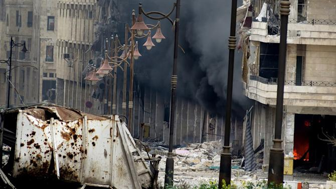 In this Tuesday March 19, 2013, citizen journalism image provided by Aleppo Media Center AMC which has been authenticated based on its contents and other AP reporting, black smoke rises from a building due to Syrian government forces shelling, in Aleppo, Syria. Syria's main opposition group demanded Wednesday a full international investigation into an alleged chemical weapons attack in the country's north, calling for a team to be sent to the village where it reportedly occurred. (AP Photo/Aleppo Media Center, AMC)