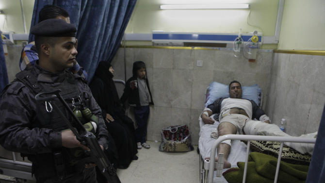 A policeman stands guard as Mohammed Abdullah, 32, lies in a hospital bed after being injured in a coordinated strike on a gold market in eastern Baghdad, Iraq, Monday, March 12, 2012. Attacks against al-Qaida's favorite targets in Iraq killed several people Monday as insurgents struck security forces, a government office and jewelry stores, demonstrating a continued threat from armed groups as the country prepares to host a meeting of the Arab world's top leaders. (AP Photo/Khalid Mohammed)