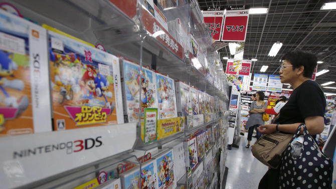 A shopper check packages of Nintendo DS game software at an electronics retail store in Tokyo, Wednesday, July 31, 2013. Nintendo reported Wednesday an 8.6 billion yen ($88 million) profit for the fiscal first quarter in a reversal from losses the previous year, thanks to a cheaper yen. (AP Photo/Shizuo Kambayashi)