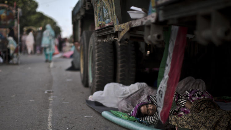 A supporter of anti-government cleric Tahir-ul-Qadri, sleeps on the ground under a truck, during a protest, in Islamabad, Pakistan, Sunday, Aug. 17, 2014. (AP Photo/Muhammed Muheisen)