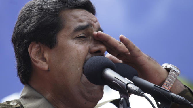 Venezuela's ruling party candidate for president and acting President Nicolas Maduro weeps as he speaks about the late President Hugo Chavez during an election campaign rally in Caracas, Venezuela, Tuesday, April 9, 2013. Maduro, Chavez's hand-picked successor, will run against opposition candidate Henrique Capriles in the upcoming Sunday, April 14 election. (AP Photo/Ramon Espinosa)