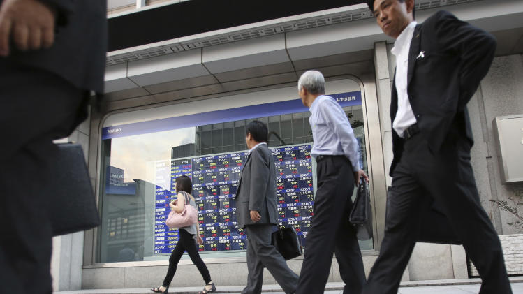 People walk by an electronic stock indicator in Tokyo Wednesday, Sept. 12, 2012 as Japan's Nikkei 225 index rose 1.7 percent to close at 8,959.96. (AP Photo/Shizuo Kambayashi)