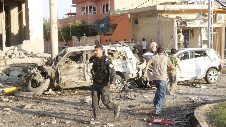 Kurdish security forces inspect the site of a car bomb attack in Kirkuk