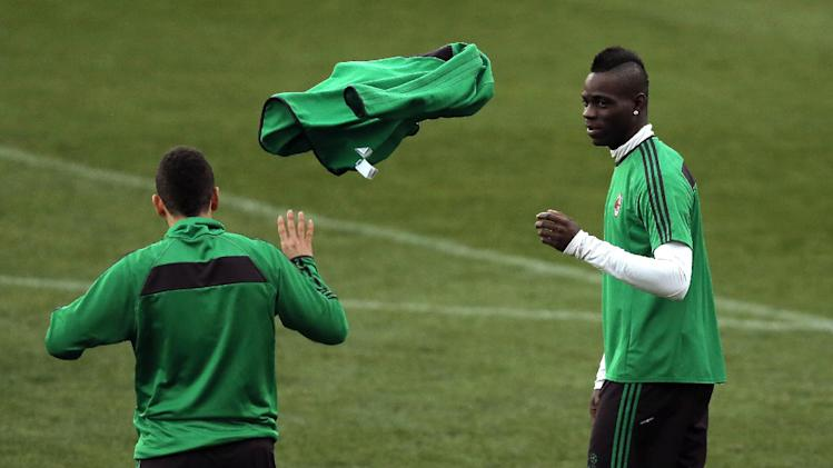 AC Milan's Mario Balotelli, right, throws an item of clothing to his teammate during a training session ahead of Tuesday's Champions League, round of 16, second leg, soccer match against Atletico Madrid at the Vicente Calderon stadium, in Madrid, Spain, Monday, March. 10, 2014
