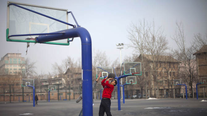 In this Saturday, Jan. 19, 2013 photo, students play basketball at their college's court in Beijing. Despite its formidable performance in recent Olympic Games, China has found itself in a crisis of declining fitness among its youngsters. (AP Photo/Alexander F. Yuan)