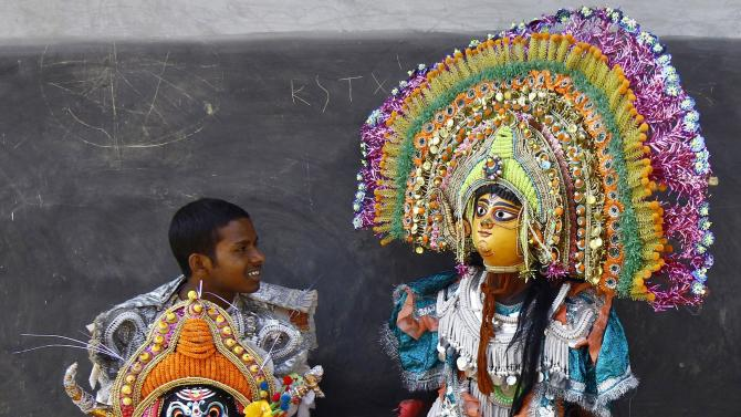 Dancers with their masks rest after taking part in the day long village festival of Chhau at Malti village in Purulia