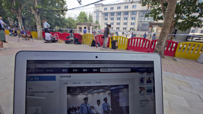 FILE - In this Thursday, Aug. 22, 2013 file photo, a website blog run by the Jinan Intermediate People's Court shows a picture of Bo Xilai attending the trial, near barricades outside the court in Jinan, in eastern China's Shandong province as the disgraced populist politician went on trial at the court on charges of bribery, embezzlement and abuse of power in a case set in motion by his wife's murder of a British businessman. China's notoriously opaque courts have suddenly embraced social media to provide a big window into their proceedings, to boost a skeptical public's confidence in the country's Communist Party-controlled legal system. (AP Photo/Ng Han Guan, File)