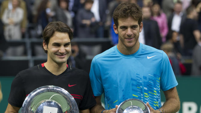 Roger Federer of Switzerland, left, and Juan Martin del Potro of Argentina hold theor trophies after the men's final at the ABN AMRO tournament at the Ahoy Arena in Rotterdam, Netherlands, Sunday, Feb. 19, 2012. Federer won in two sets 6-1, 6-4. (AP Photo/Peter Dejong)
