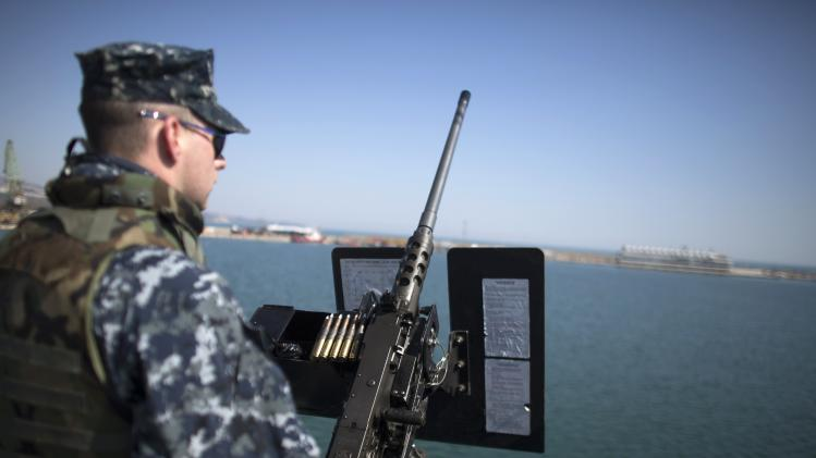 U.S. Navy personnel stands guard near a machine gun on board the USS Truxtun, a U.S. guided-missile destroyer, at the Black Sea port of Varna