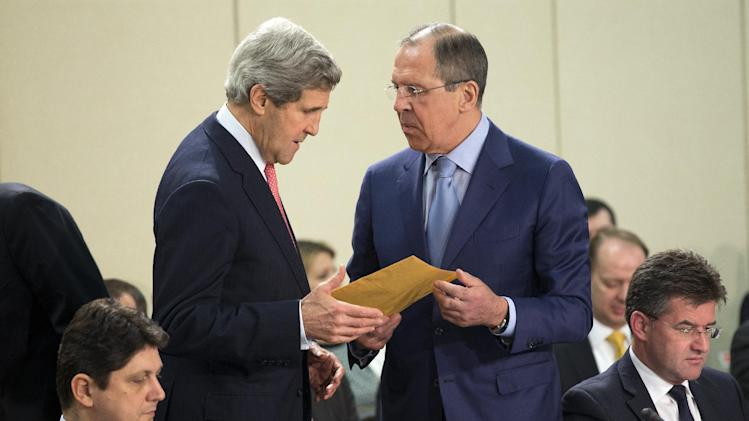 Russian Foreign Minister Sergei Lavrov, right, hands a folder to U.S. Secretary of State John Kerry before the start of the NATO-Russia Council meeting at NATO headquarters on Tuesday, April 23, 2013, in Brussels, Belgium.  (AP Photo/Evan Vucci, Pool)