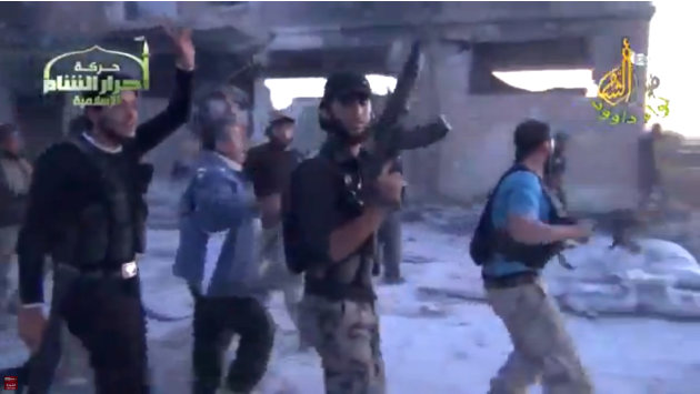 In this image from amateur video obtained by a group which calls itself Ugarit News, shows rebel fighters celebrating after purportedly capturing an army base in Nairab, northwestern Syria, Thursday,