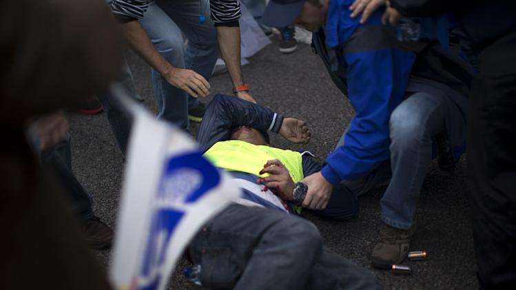 A demonstrating police officer lies on the ground after a firework he was set to throw exploded on his hand during a protest in front of the Interior Ministry in Madrid, Spain, Saturday, Oct. 27, 2012. About 3,000 off-duty police officers are demonstrating in Madrid to protest the government's austerity measures, including the cancellation of their Christmas bonuses. (AP Photo/Emilio Morenatti)