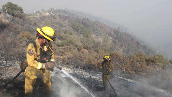 Firefighter Dennis  Navle, left, hoses down a smoking log as he and Robert Smith work hot spots of the Ponderosa Fire near Paynes Creek,  Calif., Thursday, Aug. 23, 2012.   More than 2,400 firefighters are battling the Ponderosa Fire that has destroyed 64 homes and burned more than 27,000 acres.(AP Photo/Rich Pedroncelli)