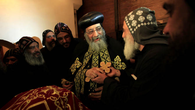 A clergyman greets Egypt's Coptic Christian pope, Tawadros II, center, during an early morning mass at the historic al-Muharraq Monastery, a centuries-old site some 180 miles (300 kilometers) south of Cairo in the province of Assiut. Egypt,Monday, Feb. 5, 2013. Egypt's Coptic Christian pope sharply criticized the country's Islamist leadership in an interview with The Associated Press on Tuesday, saying the new constitution is discriminatory and Christians should not be treated as a minority. (AP Photo/Khalil Hamra)
