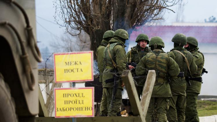 Armed men, believed to be Russian servicemen, stand guard outside Ukrainian military base in Perevalnoye