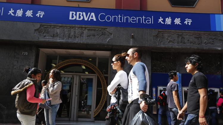 Pedestrians walk past a BBVA Continental bank branch in Lima's Chinatown