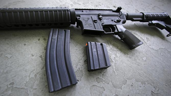 A 30 round magazine, left, and a 10 round magazine, right, rest below an AR-15 rifle at the Ammunition Storage Component company in New Britain, Conn., Wednesday, April 10, 2013. In the wake of Connecticut lawmaker's vote to ban high-capacity magazines after their passage of restrictive gun control law, the U.S. Senate is debating gun control legislation. (AP Photo/Charles Krupa)