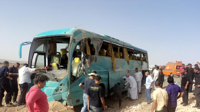 Tourists, workers and first responders stand near a bus carrying Mexican tourists after it overturned Friday, May 31, 2013 in Egypt's Sinai Peninsula before bursting into flame, killing many, according to the state news agency MEAN. Head of emergency services for South Sinai governorate Khaled Abou Hashem says that the bus was carrying tourists from the peninsula's Saint Catherine's monastery to the Red Sea resort of Dahab.(AP Photo)