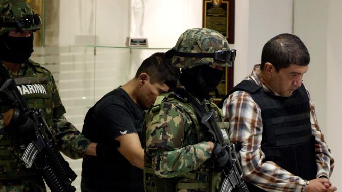 """The alleged leader of a faction of the hyper-violent Zetas cartel, Ivan Velazquez Caballero, known as """"El Taliban,"""" right,  is escorted to a media presentation at the Mexican Navy's Center for Advanced Naval Studies in Mexico City,Thursday, Sept. 27, 2012. Velazquez Caballero allegedly has been fighting a bloody internal battle with top Zetas' leader Miguel Angel Trevino Morales, and officials have said the split was behind a recent surge in massacres and shootouts, particularly in northern Mexico. (AP Photo/Eduardo Verdugo)"""