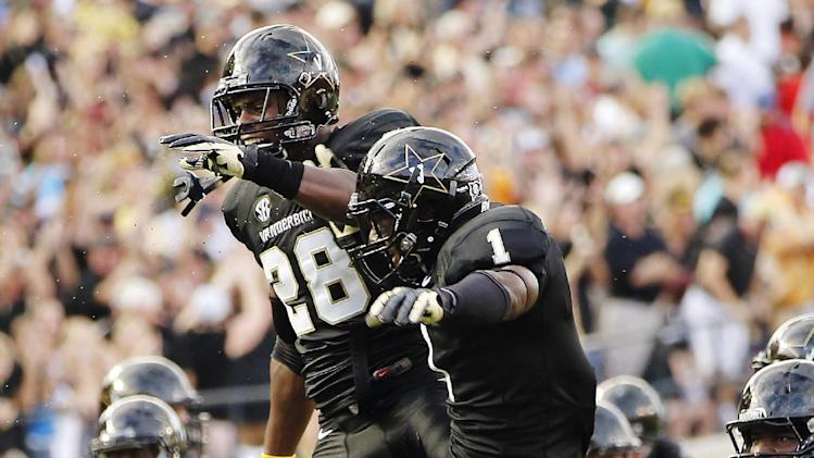 Vanderbilt's Kenny Ladler (1) celebrates his interception with Karl Butler (28) against South Carolina in the first half of an NCAA college football game, Thursday, Aug. 30, 2012, in Nashville, Tenn. (AP Photo/John Russell)