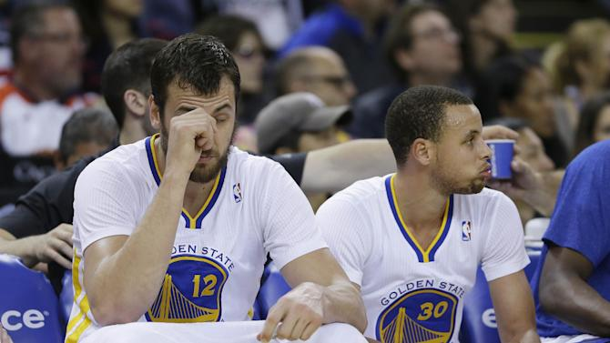 Golden State Warriors center Andrew Bogut, left, and guard Stephen Curry, right, rest on the bench during the third quarter of their NBA basketball game against the San Antonio Spurs Saturday, March 22, 2014, in Oakland, Calif. San Antonio won the game 99-90