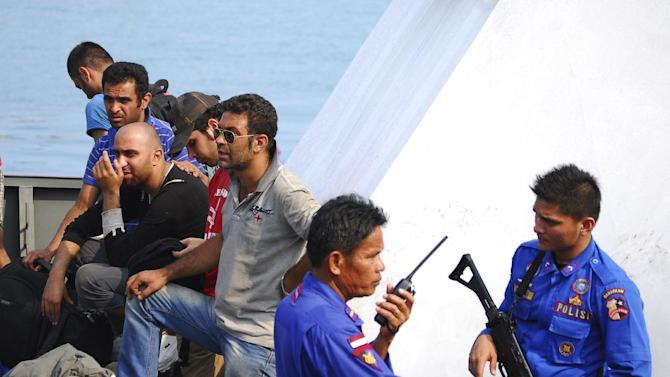 In this Oct. 12, 2012, file photo, Indonesian police officers guard asylum seekers on a patrol boat upon arrival at a port in Merak, Banten province, Indonesia. More than 60 asylum seekers from Pakistan, Iraq, and Afghanistan were on a boat en-route to Australia when they were caught and detained by Indonesian authorities. Two recent shipwrecks in the Mediterranean Sea believed to have taken the lives of as many as 1,300 asylum seekers and migrants has highlighted the escalating flow of people fleeing persecution, war and economic difficulties in their homelands. (AP Photo, File)