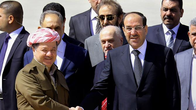 Iraqi Prime Minister Nouri al-Maliki, right, shakes hands with Kurdish regional President Massoud Barzani, left, upon his arrival in Irbil, 350 kilometers (217 miles) north of Baghdad, Iraq, Sunday, June 9, 2013. Prime Minister Nouri al-Maliki landed in Iraq's self-ruled northern Kurdish region to hold a Cabinet meeting as part of an initiative started last year to hold meetings outside Baghdad to better understand the needs of the provinces. (AP Photo/ Ceerwan Aziz)