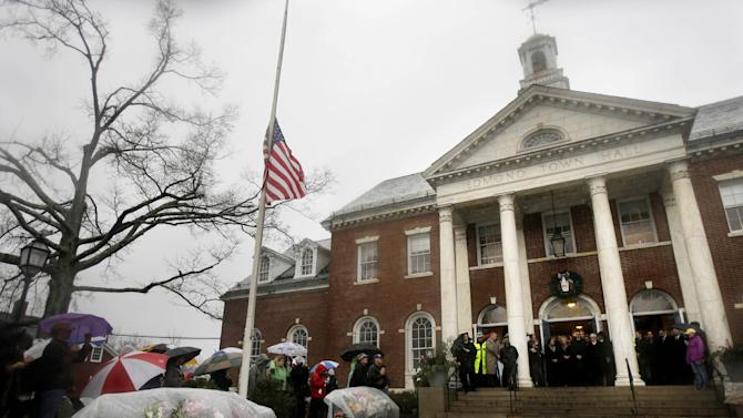 Officials including Connecticut Governor Dan Malloy observe a moment of silence on the steps of Edmond Town Hall while bells ring 26 times in Newtown, Conn., Friday, Dec. 21, 2012.   The chiming of bells reverberated throughout Newtown, commemorating one week since the crackle of gunfire in a schoolhouse killed 20 children and six adults in a massacre that has shaken the community and the nation. (AP Photo/Seth Wenig)