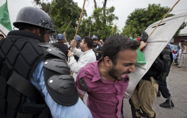 A Shi'ite Muslim supporter of the Imamia Students Organization (ISO) shouts slogans as he scuffles with police while running towards the U.S embassy with others during an anti-American protest rally in Islamabad September 14, 2012. Some 200 protesters gathered to take part in the protest to condemn a film being produced in the U.S. that insults Prophet Mohammad.   REUTERS/Mian Khursheed  (PAKISTAN - Tags: CIVIL UNREST POLITICS RELIGION)