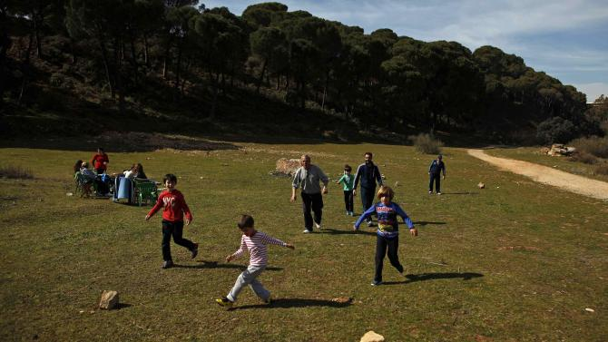 A family plays soccer in a field during Andalusia Day festivities on the outskirts of Ronda, near Malaga