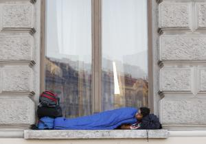 A young man sleeps in a window as migrants rest near…