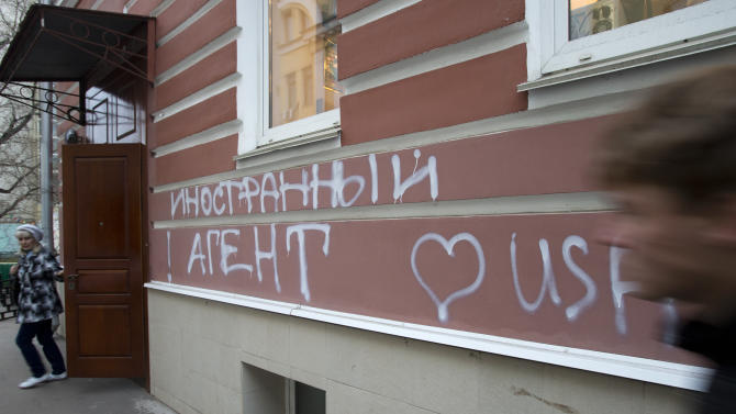 "A man passes by the office of Memorial rights group in Moscow, Russia, Wednesday, Nov. 21, 2012. The building has the words ""Foreign Agent (Loves) USA"" spray-painted on its facade by unidentified people. A new law requiring non-government organization receiving money from abroad to register as ""foreign agents"" came into force in Russia on Wednesday. (AP Photo/Misha Japaridze)"