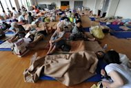 People are seen resting at a shelter in Aso City, Kumamoto prefecture, on July 17, following torrential rainfall. Flood victims have begun a full-scale clean-up operation after record rainfall forced hundreds of thousands to flee and left at least 32 dead or missing
