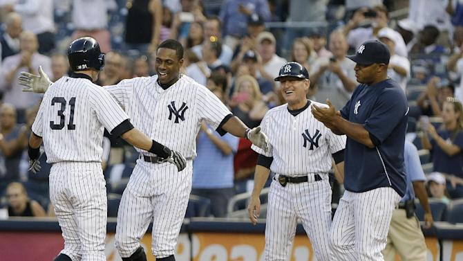New York Yankees' Curtis Granderson, second from left, first base coach Mick Kelleher, second from right, and Vernon Wells, right, congratulate Ichiro Suzuki after he hit a single for his 4,000th career hit in Japan and the major leagues, during the first inning of a baseball game against the Toronto Blue Jays on Wednesday, Aug. 21, 2013, in New York. (AP Photo/Frank Franklin II)