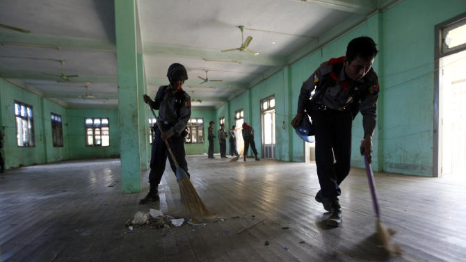 Myanmar police officers clean up floors in a  damaged mosque following fresh anti-Muslim violence broke out in Okkan, 64 kilometers (40 miles) north of Yangon, Myanmar, Wednesday, May 1, 2013. Hundreds of rampaging Buddhists armed with bricks on Tuesday, stormed a clutch of Muslim villages in the country's latest outbreak of anti-Muslim violence. (AP Photo/Khin Maung Win)