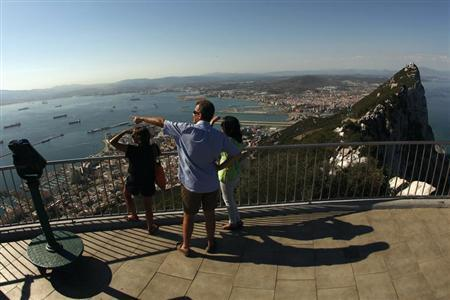 Tourists stand on a terrace of the Rock, a monolithic limestone promontory, in the British overseas territory of Gibraltar, south of Spain