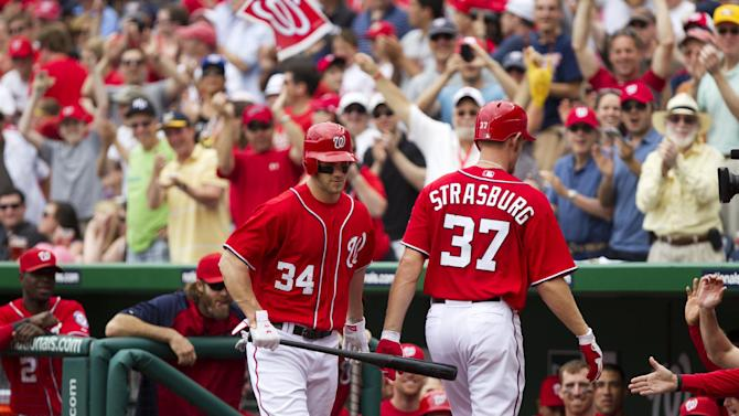 Washington Nationals starting pitcher Stephen Strasburg (37) is patted with a bat by teammate Bryce Harper (34) after hitting his first career home run during the fourth inning of a baseball game against the Baltimore Orioles in Washington, Sunday, May 20, 2012. (AP Photo/Manuel Balce Ceneta)