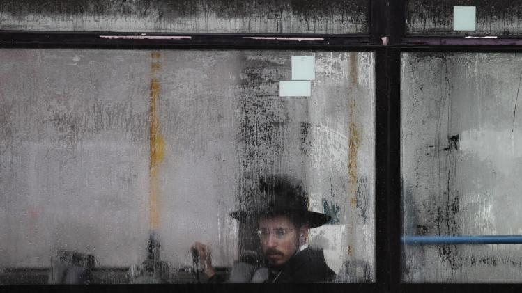An ultra-Orthodox Jewish man looks out from a condensation-covered window of a bus in Jerusalem