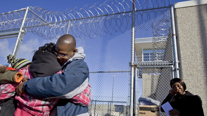 FILE- In this Jan. 30, 2009, file photo Robert Lee Stinson, second right, hugs a family friend as his sister Charlene Stinson, right, wipes her tears after Stinson walked out of the New Lisbon, Wis., Correctional Institution. Stinson was convicted in 1985 of raping and killing a 63-year-old Milwaukee woman and sentenced to life in prison. Stinson was exonerated and released in 2009 after more than 23 years in prison. (AP Photo/Andy Manis, File)