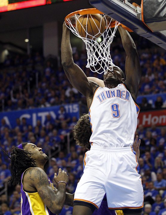 Oklahoma City Thunder forward Serge Ibaka (9) dunks in front of Los Angeles Lakers center Jordan Hill, left, and forward Pau Gasol, rear, in the first quarter of Game 5 in their NBA basketball Western