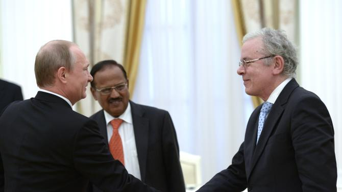 Russian President Vladimir Putin, left, shakes hands with Brazilian Ambassador to Russia Antonio Jose Vallim Guerreiro during a meeting with the BRICS countries' senior officials in charge of security matters, in the Kremlin in Moscow, Russia, Tuesday, May 26, 2015. In center is India's National Security Adviser Ajit Kumar Doval. (Alexei Nikolsky/RIA-Novosti, Kremlin Pool Photo via AP)