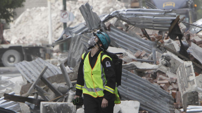 A New Zealand Urban Search and Rescue worker walks through the central business district during a search of earthquake damaged buildings in Christchurch, New Zealand, Wednesday, March 2, 2011. Police said the death toll from the quake had reached 158 and was expected to rise further following the Feb. 22. 2011, 6.3 magnitude temblor. Around 200 people are listed as missing.  (AP Photo/Mark Baker, Pool)